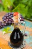 在一个玻璃水罐的黑老香醋用新鲜的红葡萄 库存图片