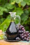 在一个玻璃水罐的黑老香醋用新鲜的红葡萄 免版税库存图片