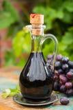在一个玻璃水罐的黑老香醋用新鲜的红葡萄 库存照片