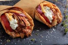 在一个黑盘的皮塔饼面包包裹的希腊电罗经 免版税库存图片