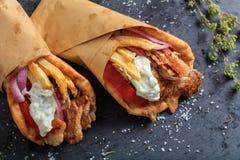 在一个黑盘的皮塔饼面包包裹的希腊电罗经 库存图片