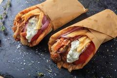 在一个黑盘的皮塔饼面包包裹的希腊电罗经 免版税库存照片