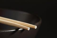在一个黑碗的两双筷子 库存照片