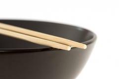 在一个黑碗的两双筷子 免版税图库摄影