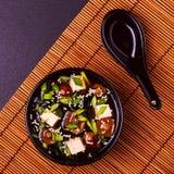 在一个黑碗的日本大酱汤在竹餐巾 库存图片