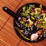 在一个黑碗的日本大酱汤在竹餐巾 图库摄影