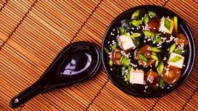 在一个黑碗的日本大酱汤在竹餐巾 库存照片