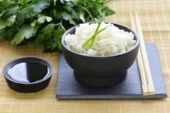 在一个黑碗的煮沸的白米 免版税库存图片