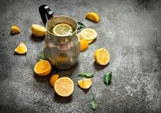 在一个水罐的冷的柠檬水有切片的柠檬和绿色叶子 免版税库存照片