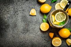 在一个水罐的冷的柠檬水有切片的柠檬和绿色叶子 库存图片
