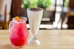 在一个水罐的红色汁液用柠檬和一个白色鸡尾酒在一块玻璃用巧克力和薄菏在一张木桌上,侧视图 库存照片