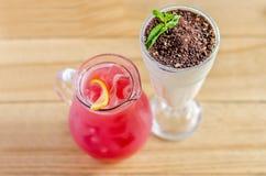 在一个水罐的红色汁液用柠檬和一个白色鸡尾酒在一块玻璃用巧克力和薄菏 免版税库存图片