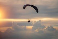 在一个滑翔伞的男孩和女孩飞行在云彩背景  免版税库存图片
