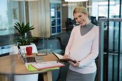 在一个组织者的怀孕的女实业家文字在办公室 图库摄影