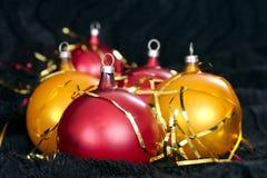 在一个黑背景的红色和黄色圣诞节球 图库摄影
