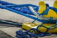 在一个黄色停泊系船柱附近的重的蓝色绳索套在码头 免版税库存图片
