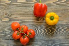 在一个绿色分支和红辣椒的五个红色蕃茄在木背景 免版税库存图片
