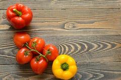 在一个绿色分支和红辣椒的五个红色蕃茄在木背景 免版税图库摄影