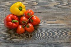 在一个绿色分支和红辣椒的五个红色蕃茄在木背景 库存图片