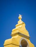 在一个黄色塔顶部的海鸥 免版税库存照片