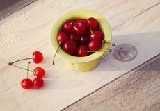 在一个黄色小杯子的新鲜的成熟樱桃在一张木桌上 免版税图库摄影