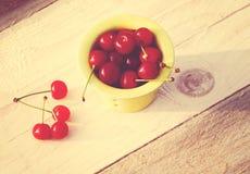 在一个黄色小杯子的新鲜的成熟樱桃在一张木桌上 免版税库存照片