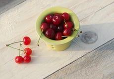 在一个黄色小杯子的新鲜的成熟樱桃在一张木桌上 图库摄影
