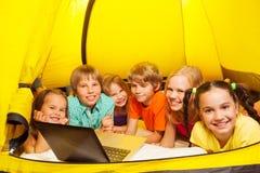 在一个黄色帐篷放置的六个孩子 免版税库存照片