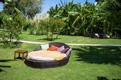 在一个绿色异乎寻常的庭院里sunbed的休息室 库存图片