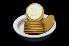 在一个黄色曲奇饼的被舔的奶油填装的面孔 免版税库存照片