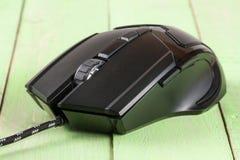 在一个绿色木背景特写镜头的黑计算机老鼠 免版税库存照片