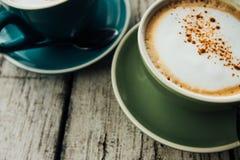 在一个绿色杯子的咖啡热奶咖啡在茶碟 两个杯子在一张木桌上的咖啡 库存图片