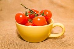 在一个黄色杯子的红色西红柿在老布料 库存照片