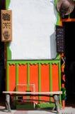 在一个绿色橙色殖民地居民前面的长木凳 库存照片