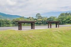 在一个绿色湖的布朗长木凳 免版税库存照片