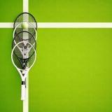 在一个黄色球附近的网球拍在一个绿色法院 库存照片