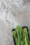 在一个黑色的盘子的新鲜的绿色硬花甘蓝 背景灰色石头 顶层 图库摄影