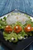 在一个黑色的盘子的盐味的三文鱼沙拉 免版税图库摄影