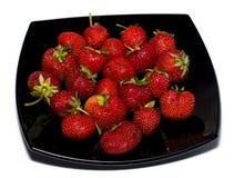 在一个黑色的盘子的自然草莓 免版税库存照片