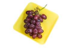 在一个黄色盘的葡萄 库存图片