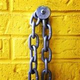 在一个黄色砖墙上的链子 免版税库存照片