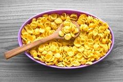 在一个紫色碗的玉米片在灰色背景 免版税库存照片