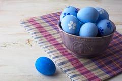 在一个紫色碗的蓝色复活节彩蛋 免版税库存图片