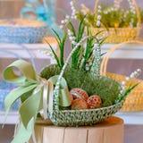 在一个绿色篮子的橙色木复活节彩蛋在残余部分 免版税库存图片