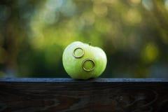 在一个绿色苹果的婚戒 免版税库存图片