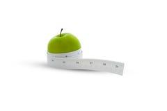 在一个绿色苹果附近被包裹的评定的磁带 库存照片