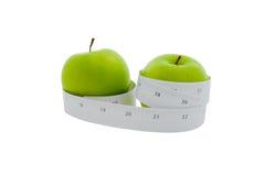 在一个绿色苹果附近被包裹的评定的磁带 免版税库存图片