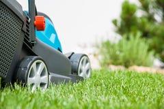 在一个绿色草甸的割草机 免版税库存图片