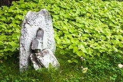在一个绿色草甸的老石十字架 免版税库存照片