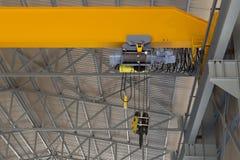 在一个黄色钢粱的室内吊车 免版税图库摄影